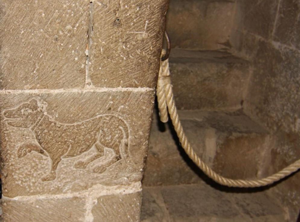 Ein in Stein gemeisselter Hund beim Eingang zur Krypta auf der Hoehenburg Loarre.