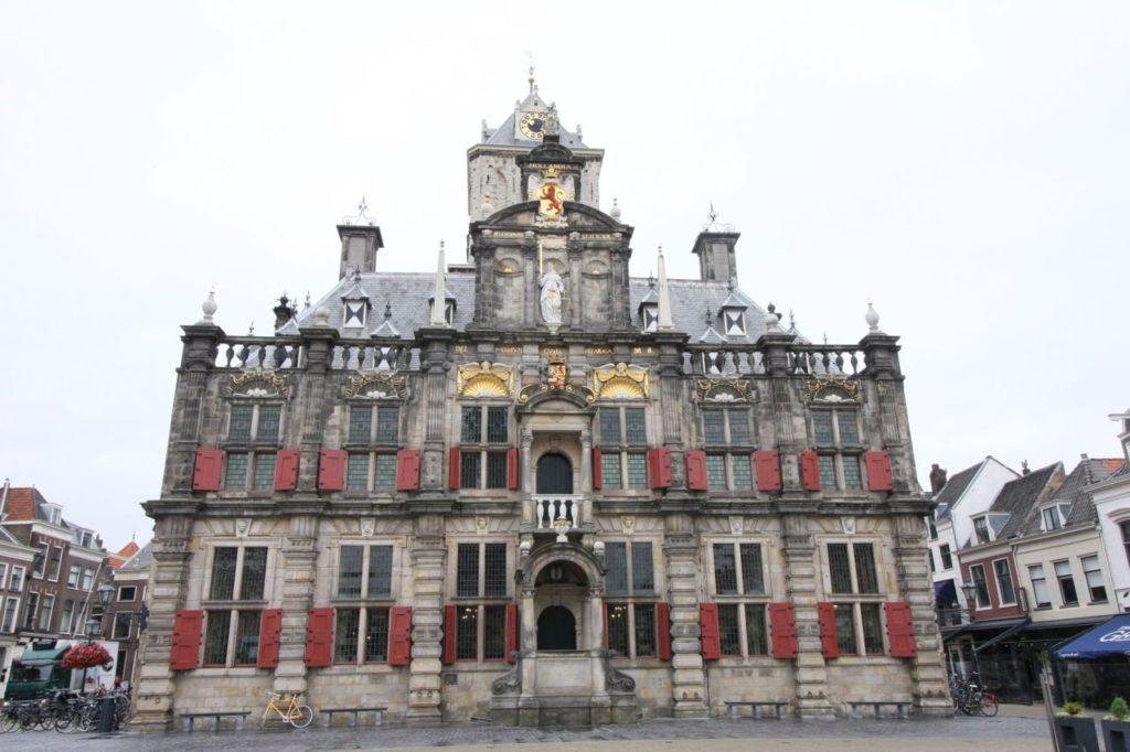 Frontansicht des Stadthauses / Rathauses mit roten Fensterlaeden in Delft
