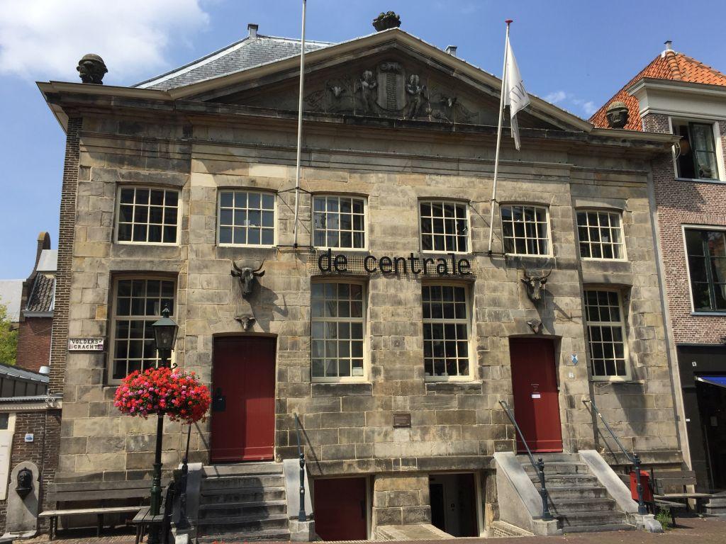 Frontansicht der ehemaligen Fleischhalle in Delft; imposantes Gebäude mit zwei Kuh- und Schafskoepfen an der Hauswand