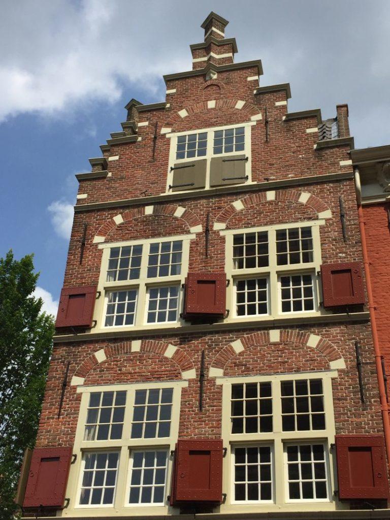 Frontansicht mit Treppengiebel und roten Fensterladen des Hauses am Markt 2 in Delft