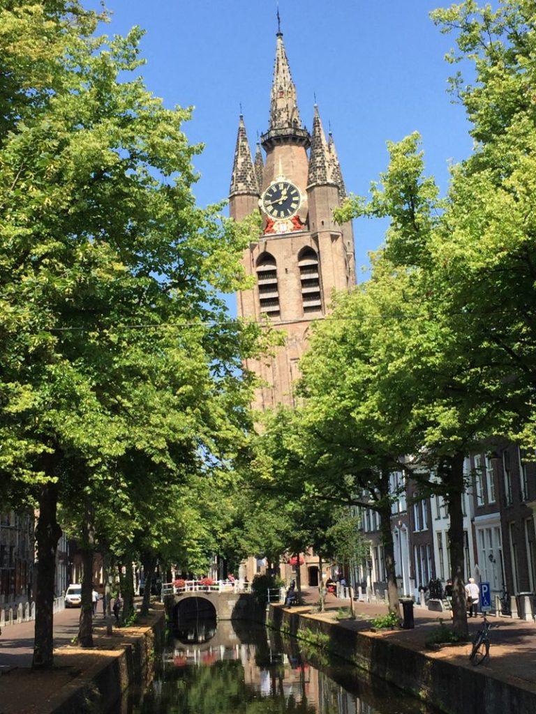 Blick vom Oude Delft Kanal auf den schiefen Turm der Oude Kerk, der Alten Kirche in Delft