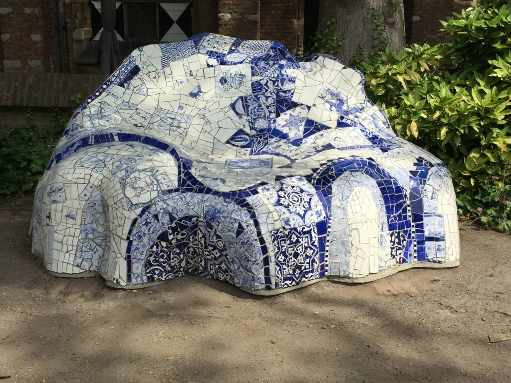 """Die blaue-weiß gekachelte Bank """"Hommage an Gaudí"""" im Garten des Prinzenhofes in Delft"""