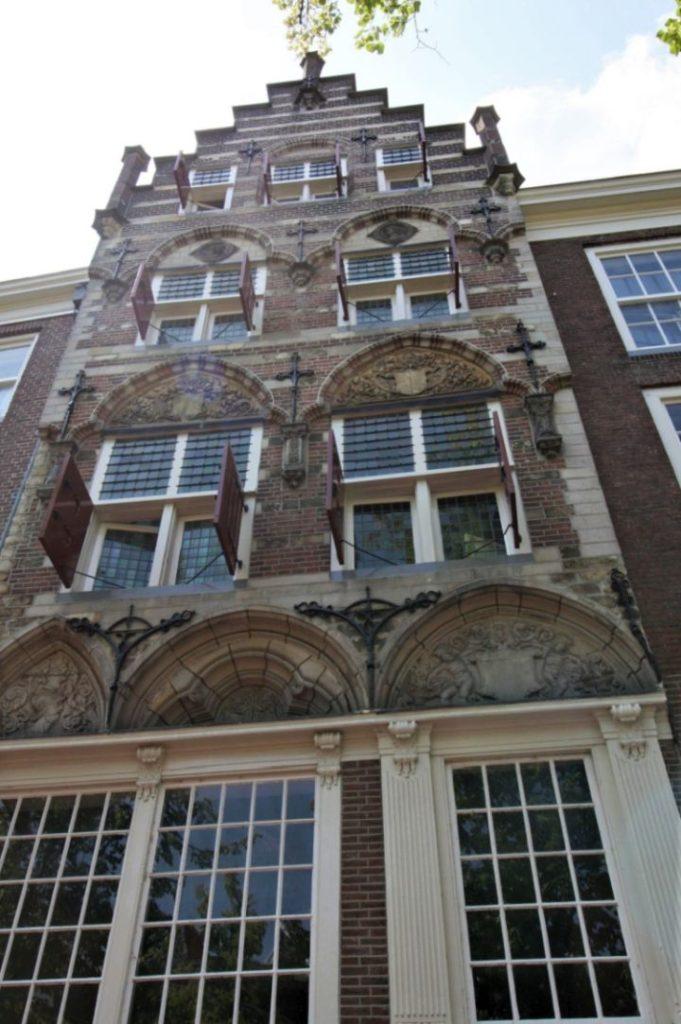 Frontansicht der ehemaligen Brauerei de Handboog in Delft, Backsteinfassade mit Treppengiebel und roten Fensterlaeden