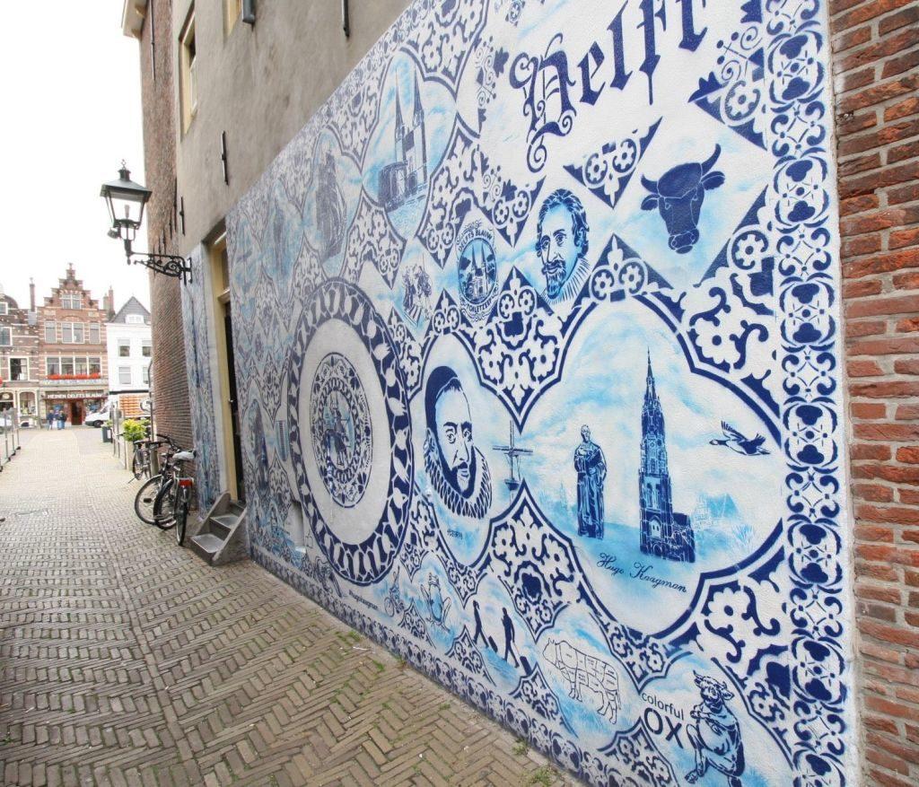 Blau-weiße Graffiti mit Delfter Motiven an der Wand im Bonte Ossteeg 22 von Hugo Kaagman