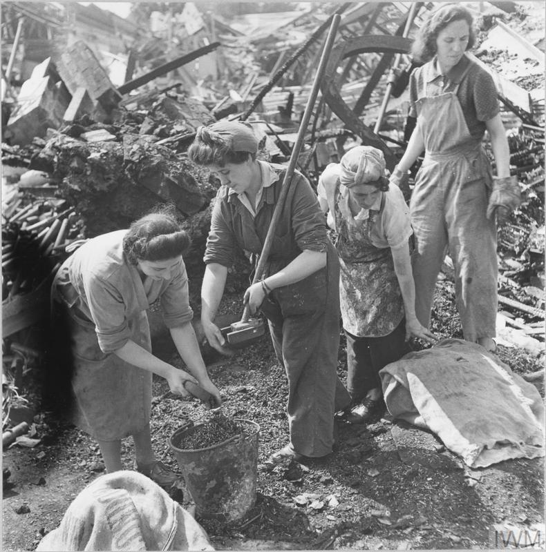 Weibliche Kriegsarbeiter retten mit Magneten Nägel aus den Trümmern einer durch Bomben beschädigten Fabrik