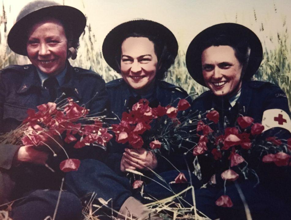 Dorothy Molly Mulholland rechts im Bild, eine der 4500 kanadischen Krankenschwestern mit zwei Kolleginnen in einem Feld voller Mohnblumen in der Normandie