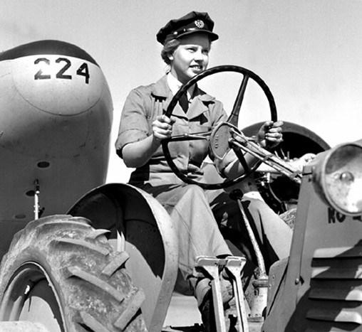 Laura Bagby von der Royal Canadian Air Force Women's Division am Steuer ihres Traktors, der ein Flugzeug zieht,