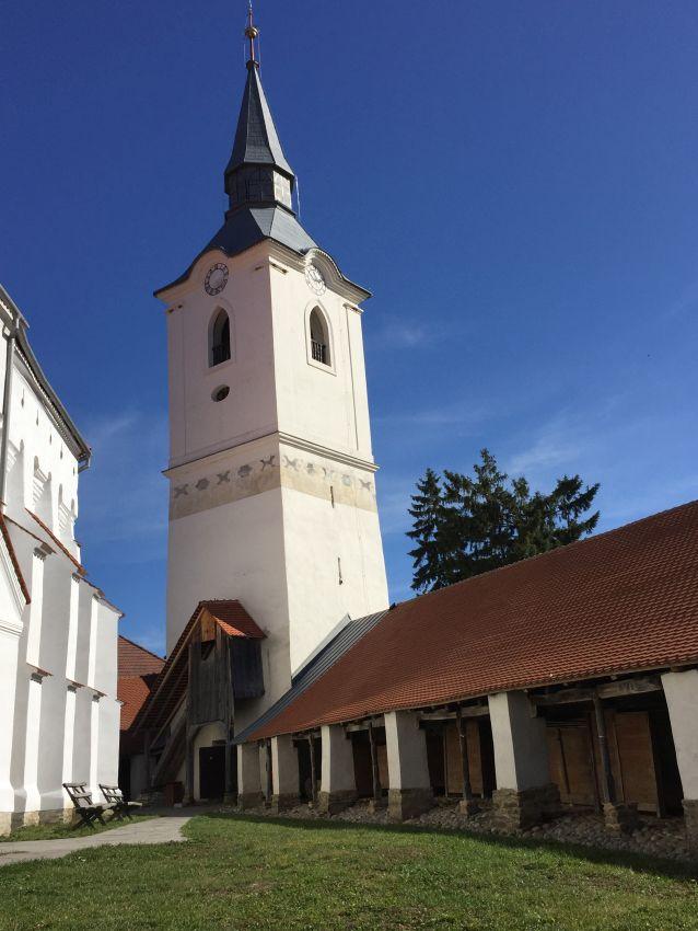 Glockenturm und Teil des Mauerrings der Wehrkirche von Dersch / Darjiu