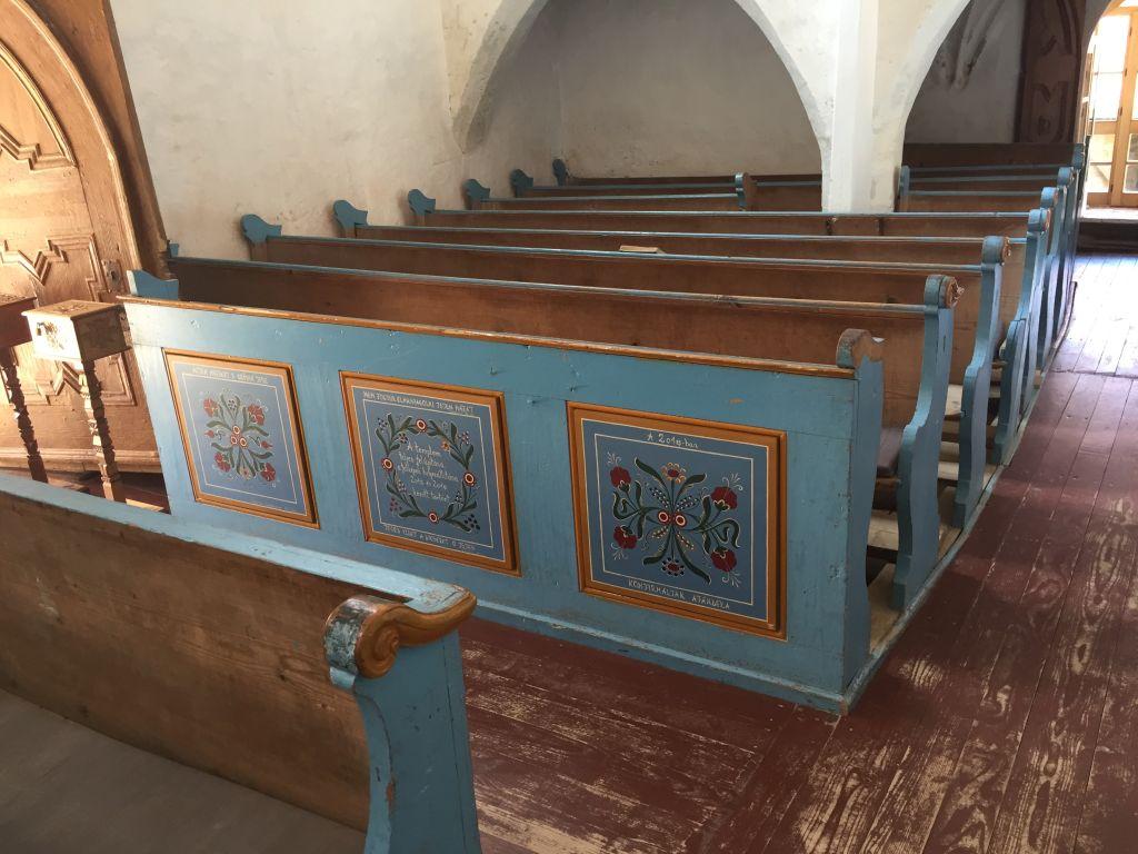 mit floralen Motiven verzierte, blau angemalte Baenke in der Wehrkirche von Dersch / Darjiu
