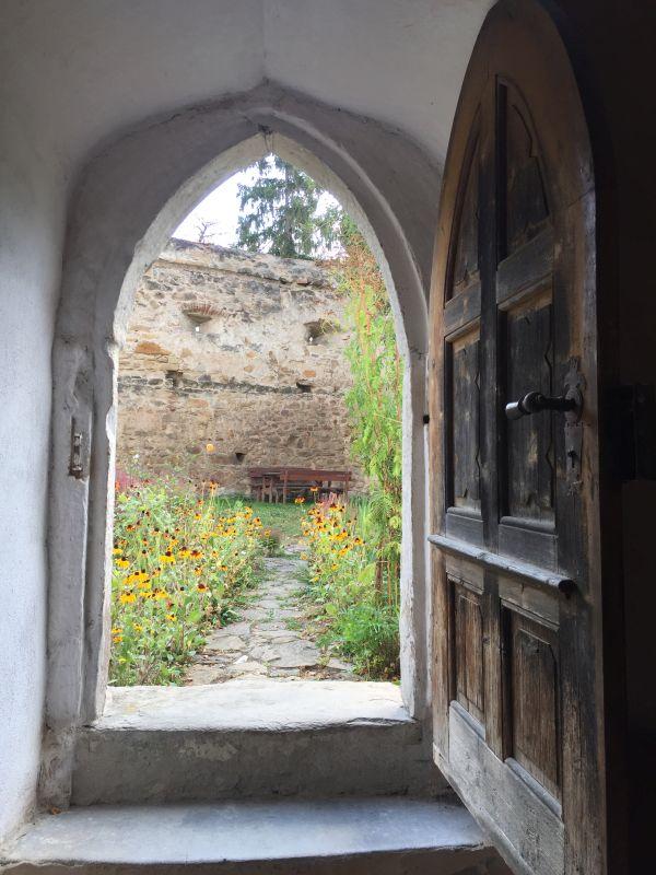 Blick aus dem Suedeingang der Wehrkirche in Kleinschenk / Cincsor auf den Kirchhof