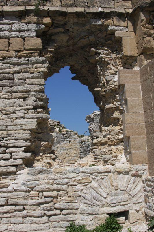 Blick durch ein Ruinenfenster in den blauen Himmel
