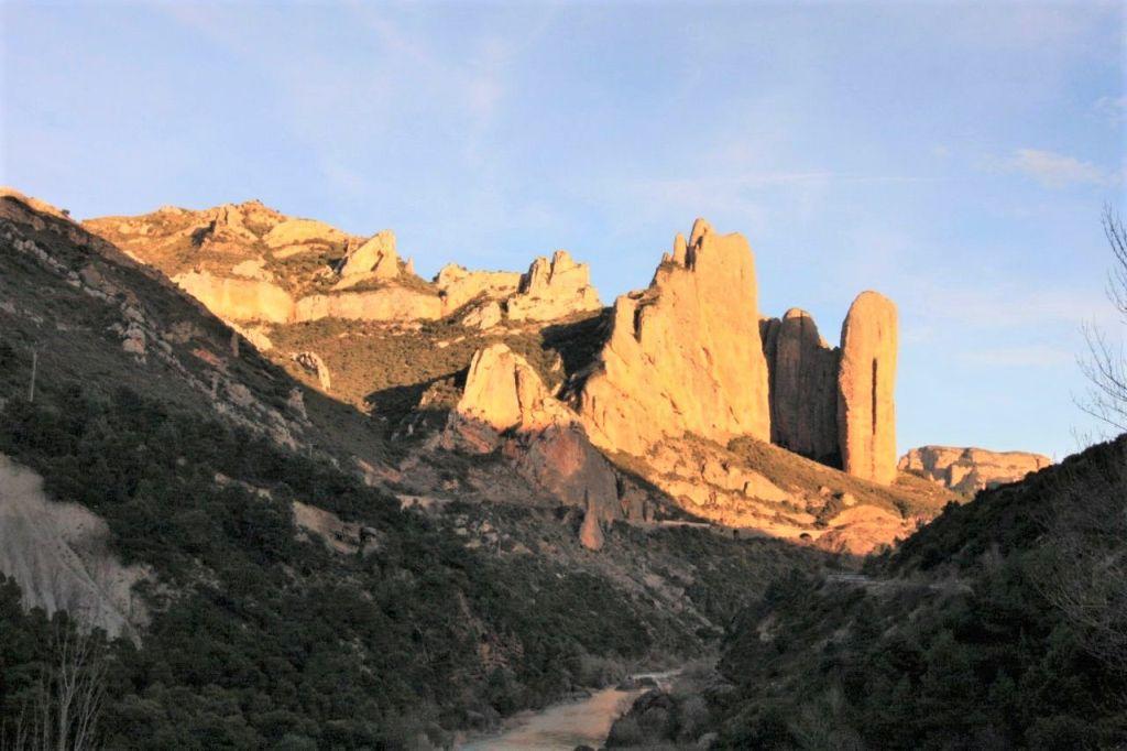 Die Abendsonne bringt die Riglos Mallos, kegelfoermige Gesteinformationen, in der Provinz Huesca zum Leuchten. In der Ebene fliesst der Río Gallego.