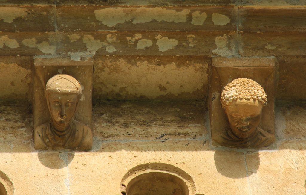 zwei menschliche Koepfe an der Klosterkirche von Irache in Ayegui
