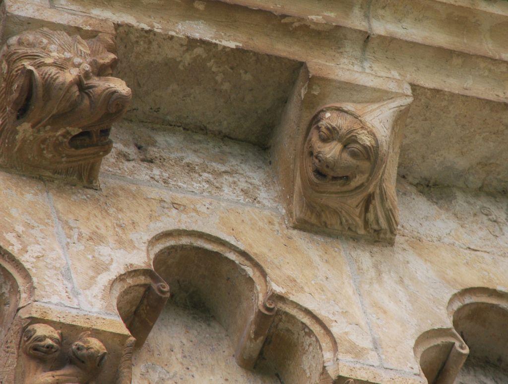 ein in Stein gemeisselter Loewe und ein Narr an der Chorwand der Klosterkirche von Irache in Navarra