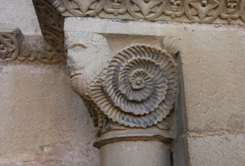 Maennerkopf mit gezwirbeltem Bart am Spiegelportal der Kirche San Miguel in Olcoz