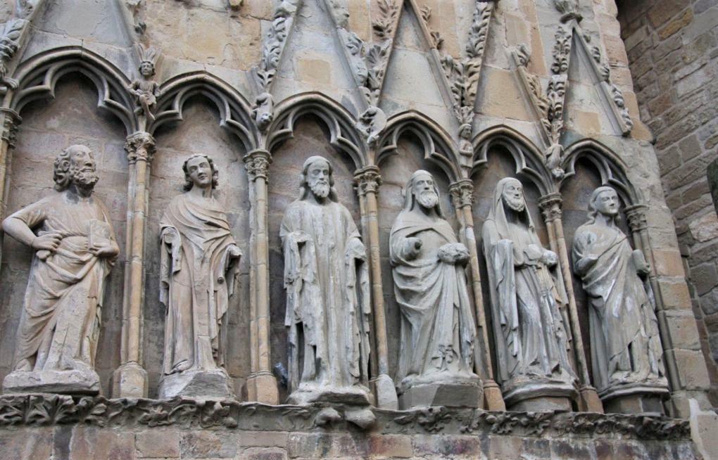 Figuren der fuenf Apostel und Jesus in Arkadenboegen der Westfassade der Kirche Santa Maria la Real in Olite