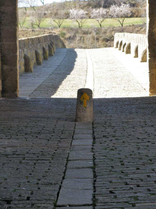 gelber Hinweispfeil fuer den Jakobsweg auf der Bruecke von Puente la Reina