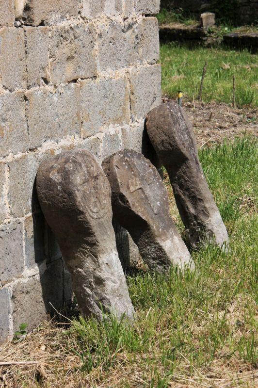 Drei mittelalterliche Begraebnis-Stelen sonnen sich an der Wand der Wehrkirche San Esteban in Roncal