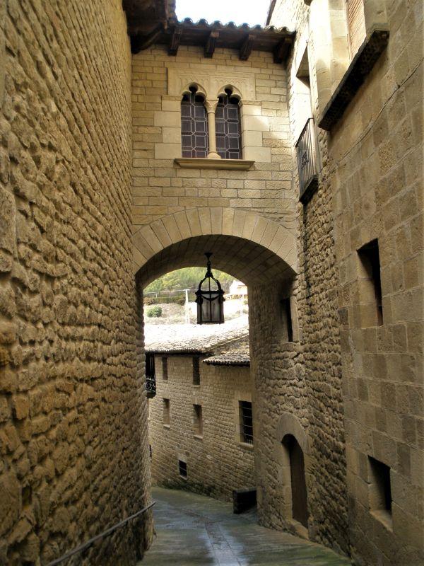 Altstadtgasse mit Torbogen, Laterne und maurischen Zwillingsbogenfenster in Uncastillo