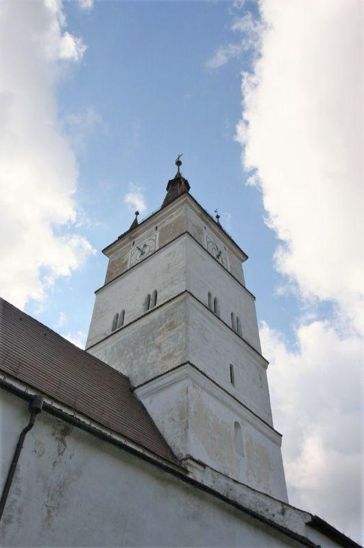 Glockenturm der Kirche von Honigberg vor blauem Himmel