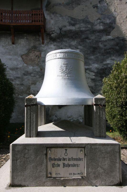Ehrenmal mit Glocke im Kirchhof der Kirchenburg von Honigberg im Burzenland