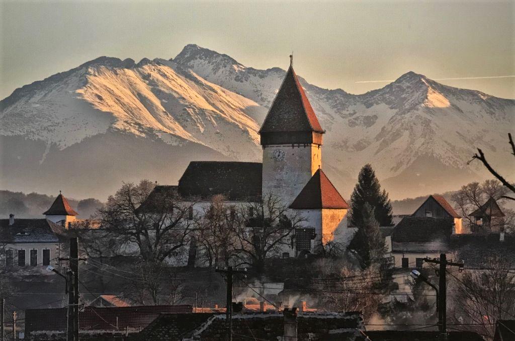 Kirchenburg von Holzmengen (Hosman) vor den schneebedeckten Karpaten; Fotografie aus dem Bildband Ueber Siebenbuergen