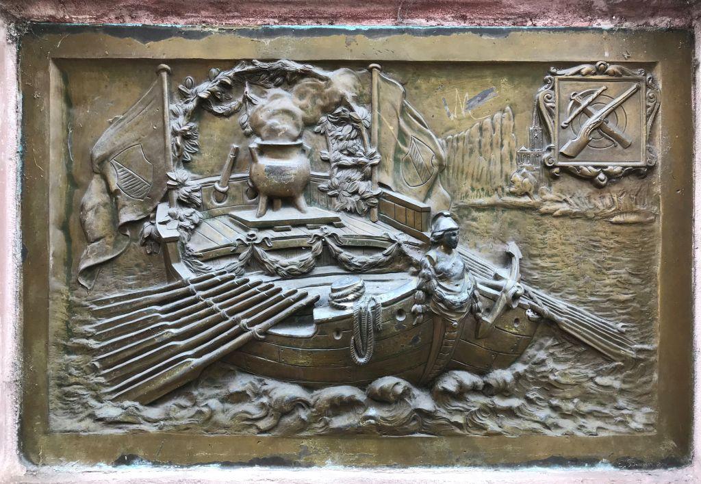 Bronzeplakette der Hirsebreifahrt auf dem Denkmal an der Place du Pont aux Chats in Strasbourg